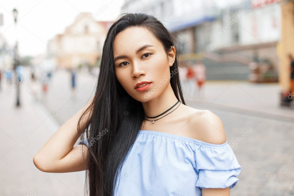 Beautiful Asian Woman With Long Hair Posing On A City Background
