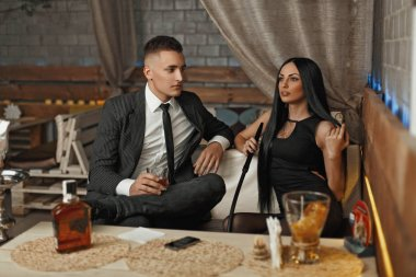 Young beautiful couple relaxing at the bar. Man drinks whiskey. Woman smokes a hookah