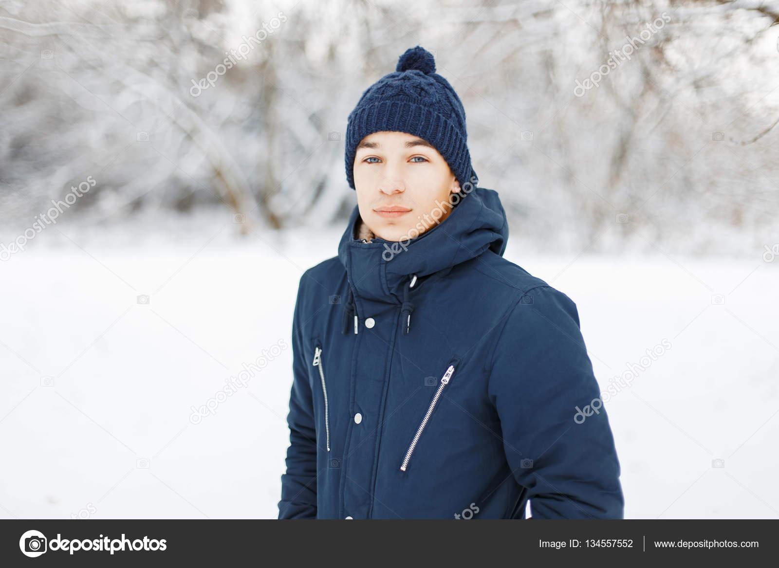 8b5bcb3e12 Jeune homme en vêtements d'hiver élégant sur un fond de parc enneigé–  images de stock libres de droits