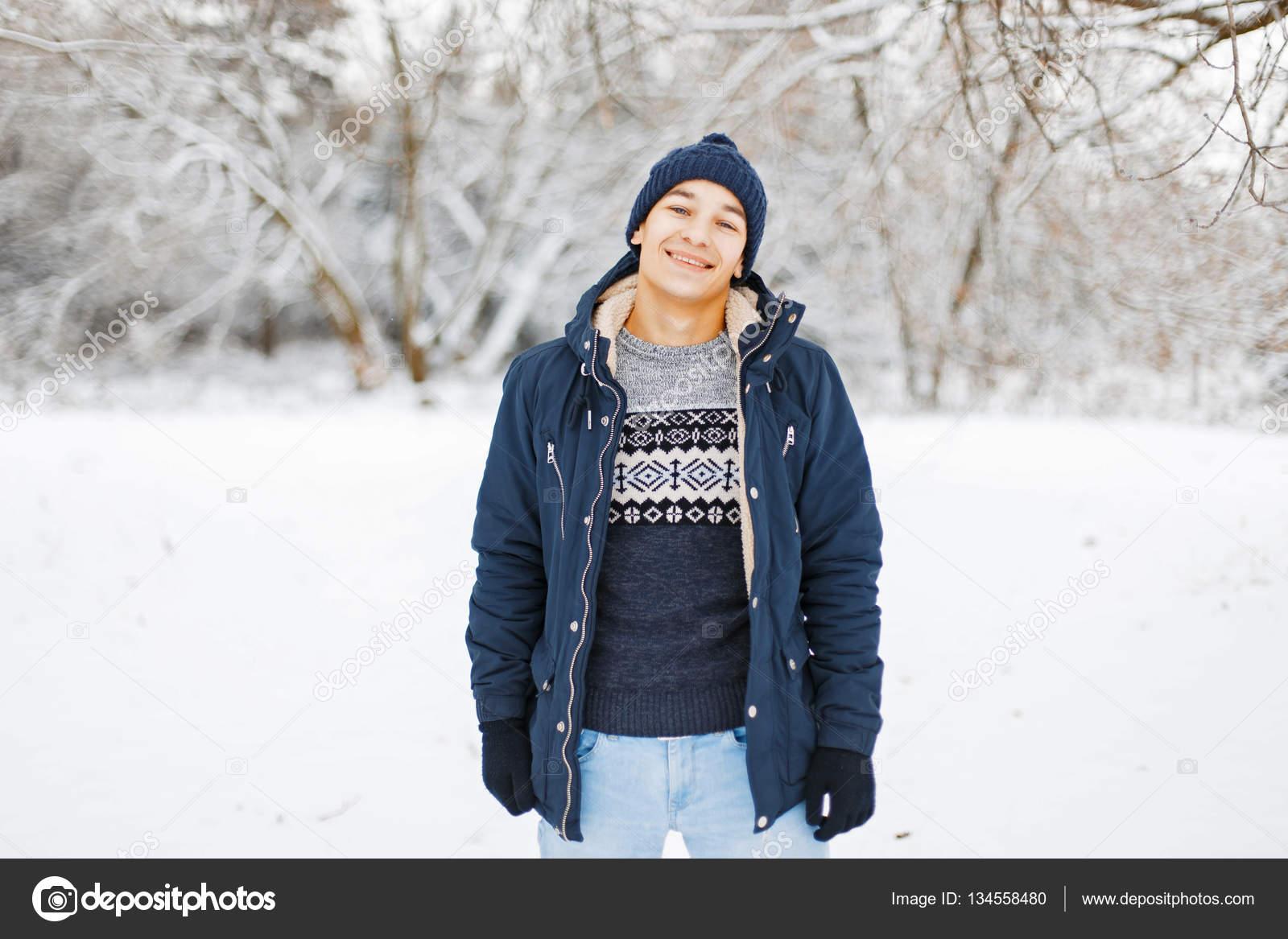 b9e2dd7e16 Heureux jeune homme en vêtements d'hiver et élégant pull à la mode, marcher  dans un parc d'hiver– images de stock libres de droits