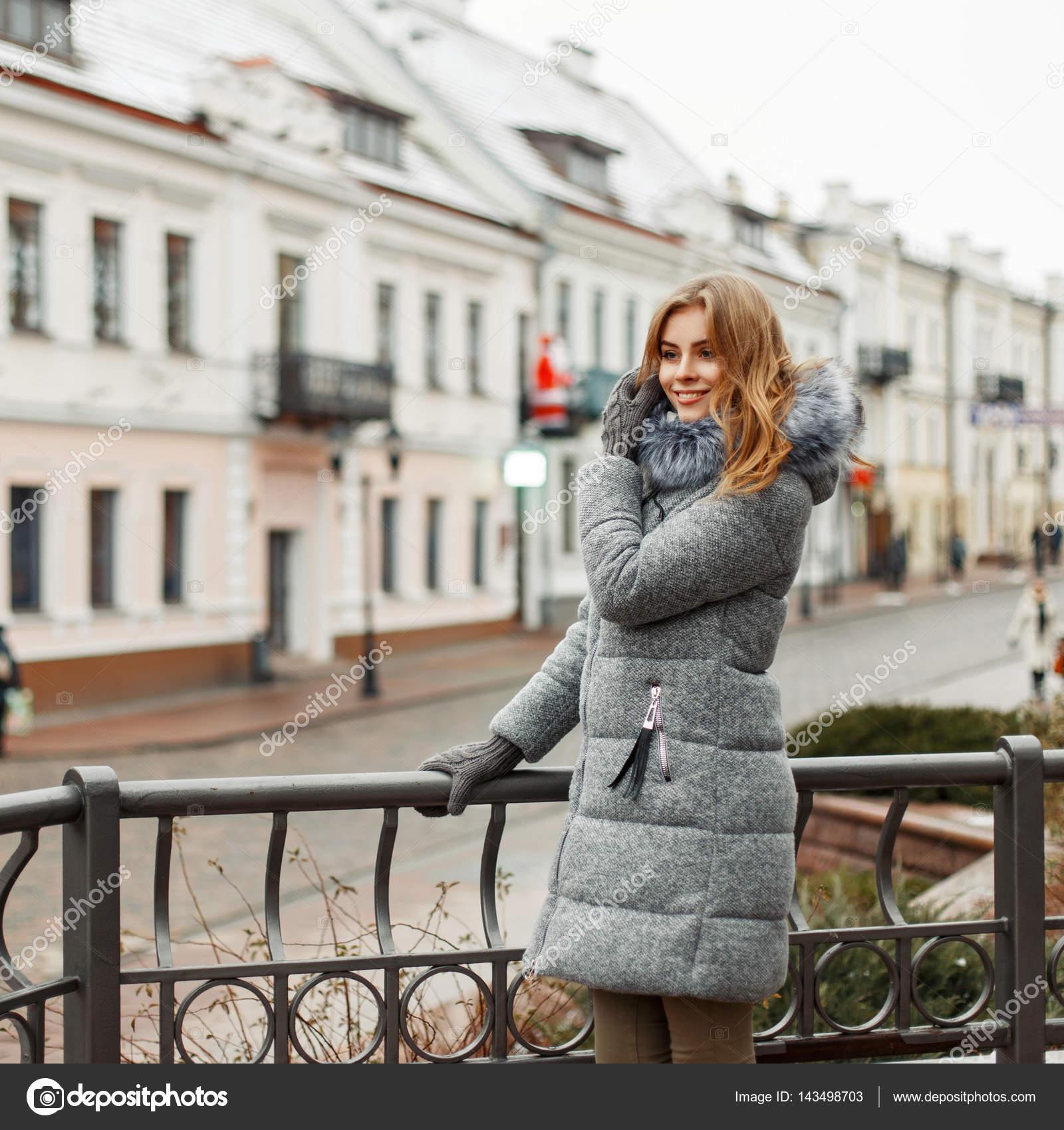 a66abd3cb0e6 Bella giovane donna in vestiti alla moda a maglia su priorità bassa della  città– immagine stock