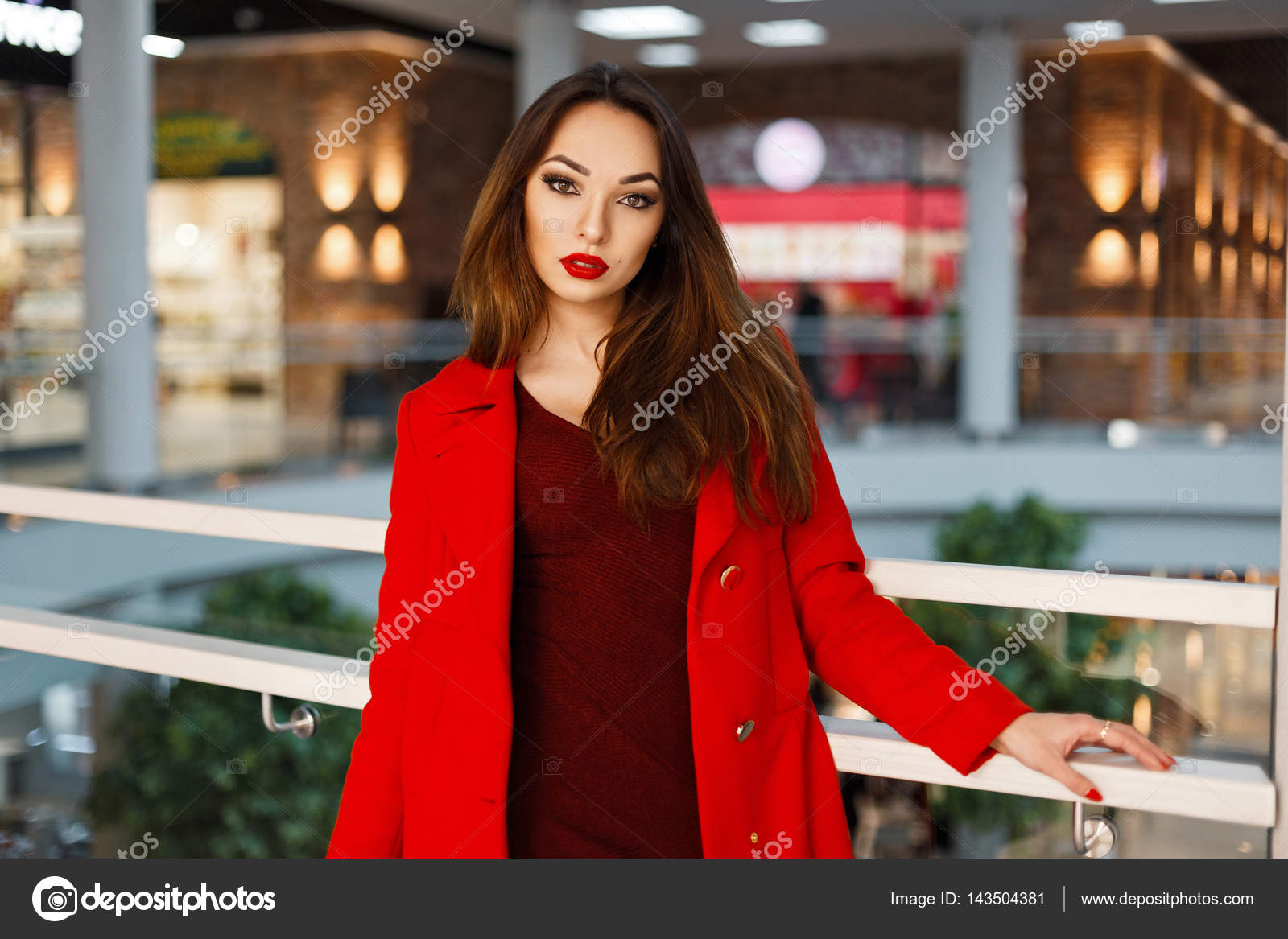 3903a09d059fb2 Junge schöne Frau in einem roten Mantel im Shop einkaufen gehen — Stockfoto