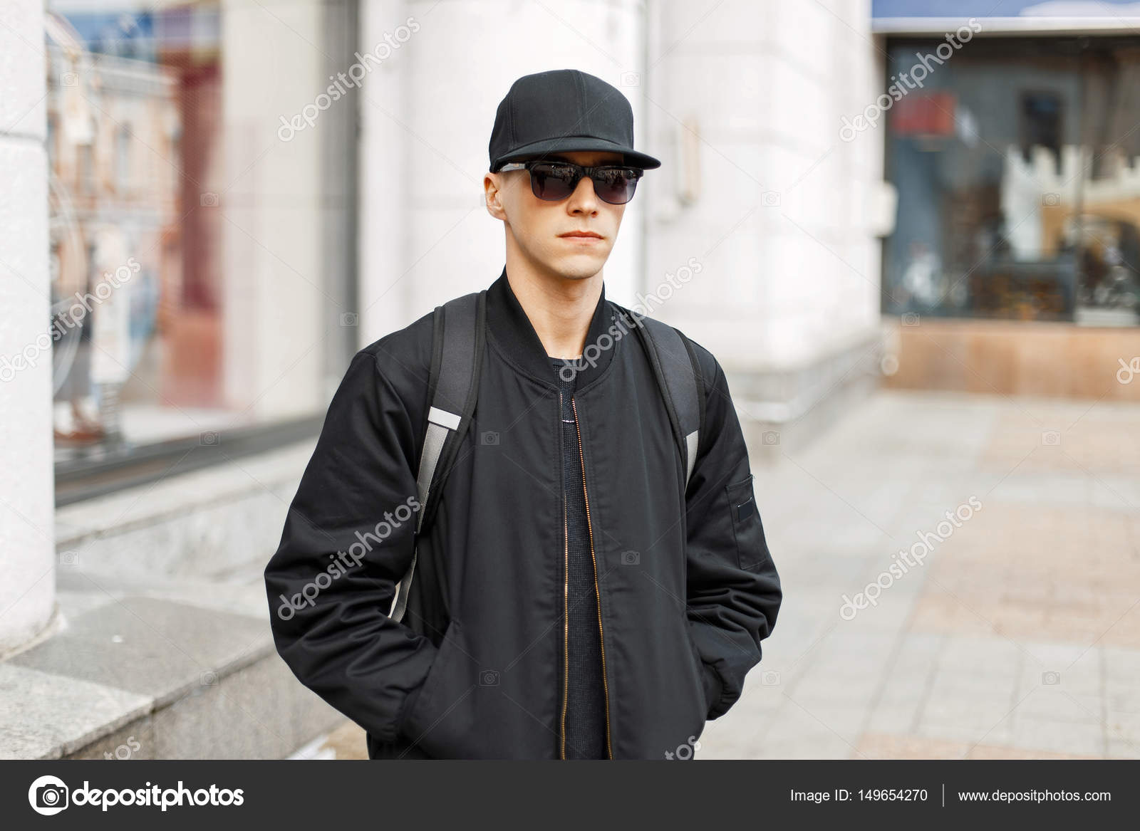 5da2d749 Handsome man in black glasses and a baseball cap, a black fashionable  jacket walks around