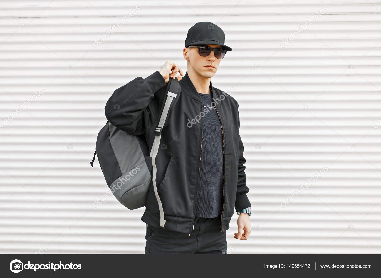 Stilvolle junge Mann in schwarz moderne Kleidung mit einem Rucksack ...