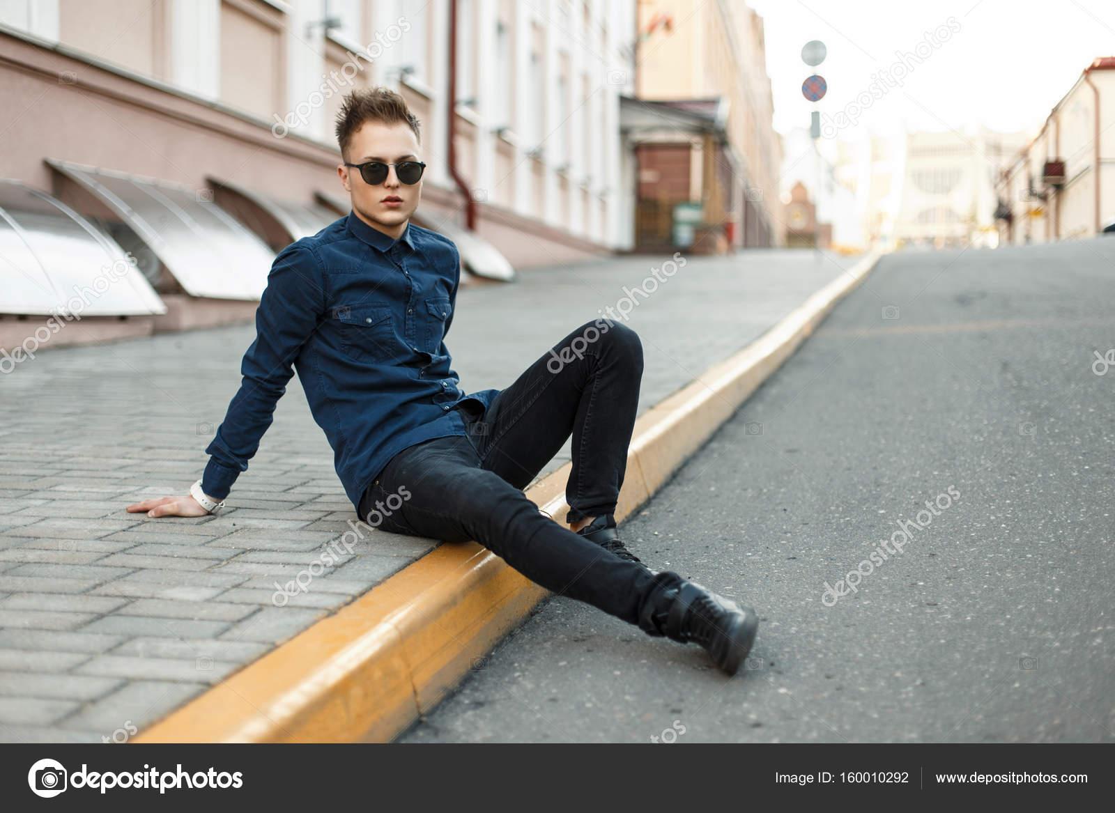 huge selection of 7f48e 5eb8a Giovane bello in una camicia blu, jeans neri e scarpe da ...