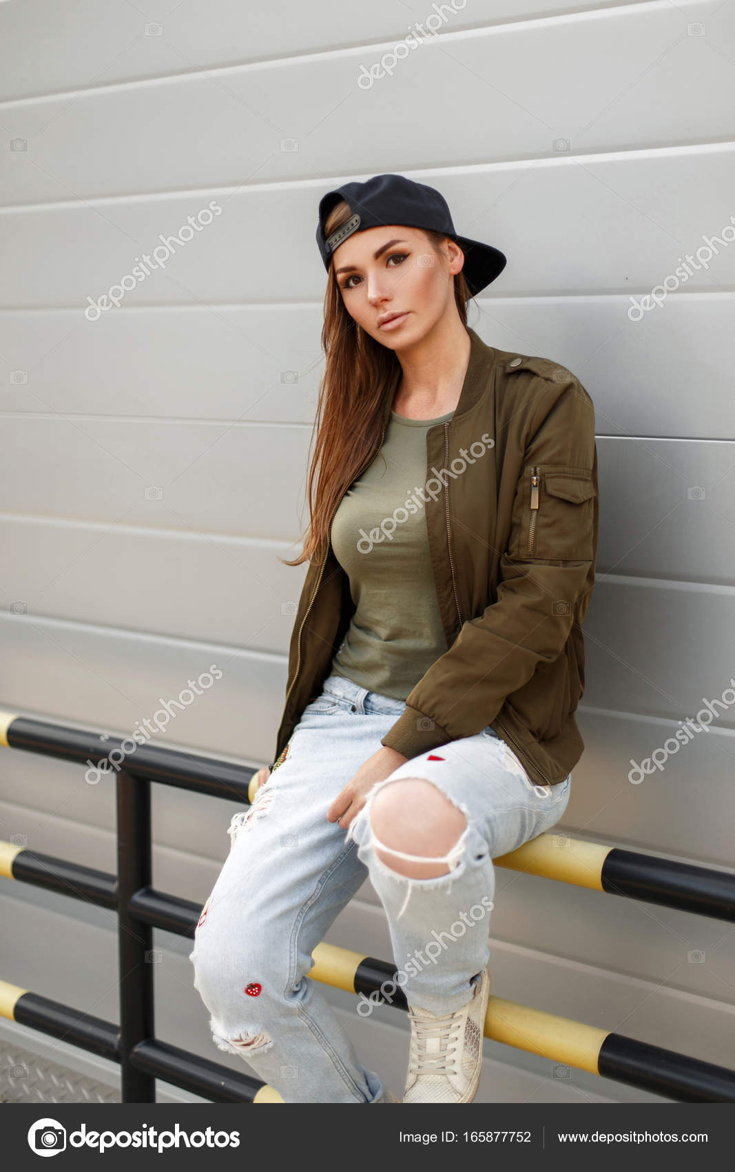 c2f45f26fe Young beautiful girl with freckles in a baseball cap in a street style in a  fashionable military green jacket and blue torn jeans sits near a metal  wall ...