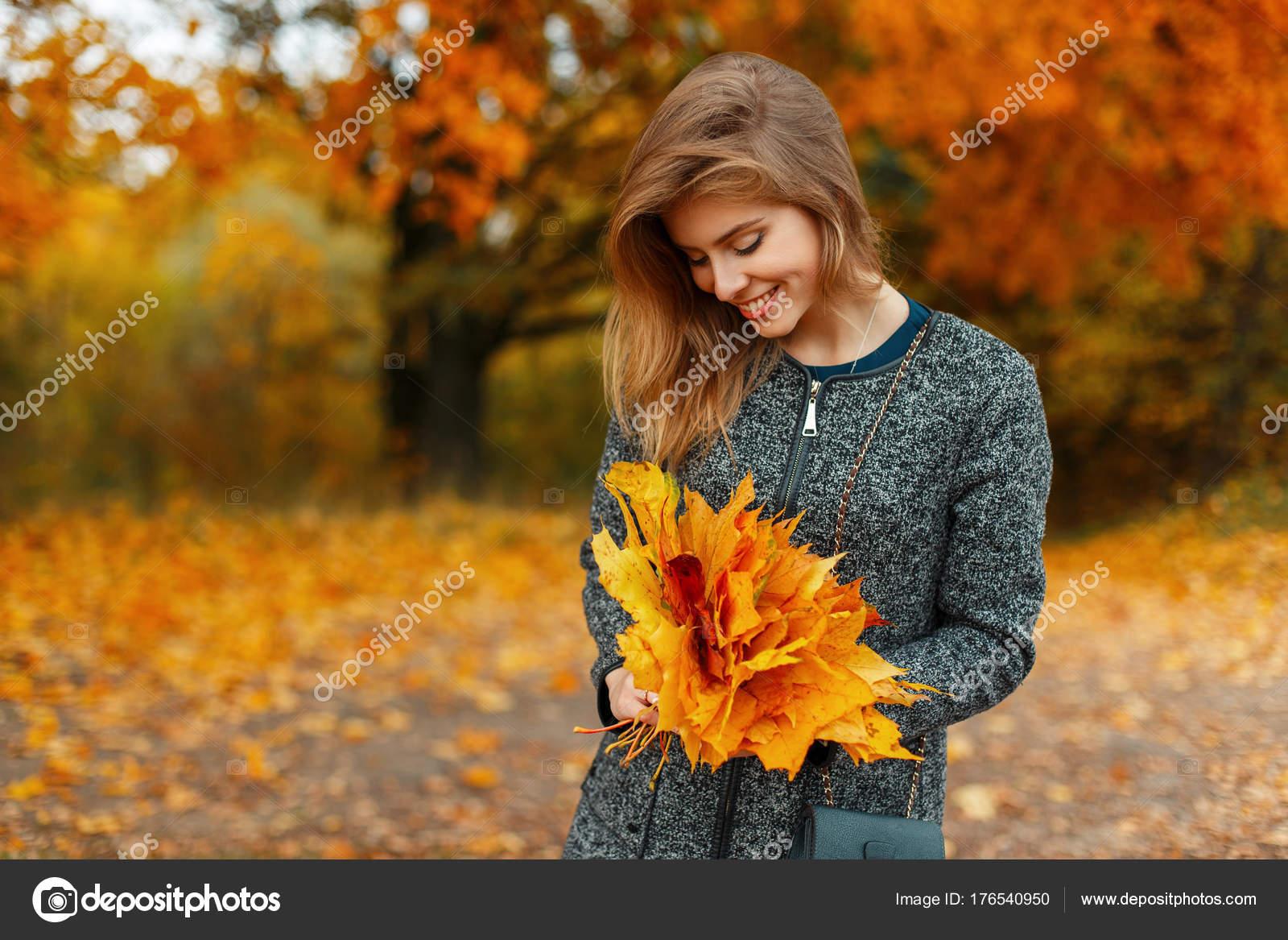 3487f09619056 Hermosa mujer feliz joven en ropa de moda otoño tiene hojas amarillas al  aire libre —