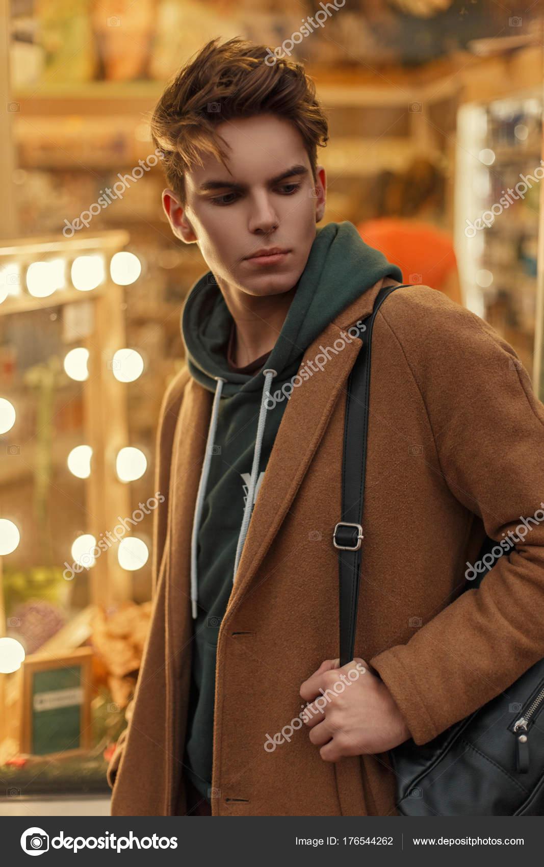 c492f18113 Giovane modello bello uomo con un taglio di capelli in un cappotto ...
