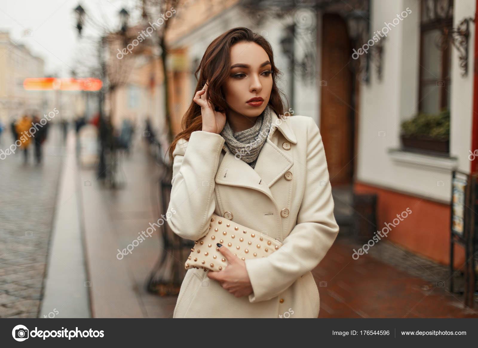 907083c52fcf Alla moda bella giovane donna in un cappotto alla moda con una borsa alla  moda camminare all aperto in città– immagine stock
