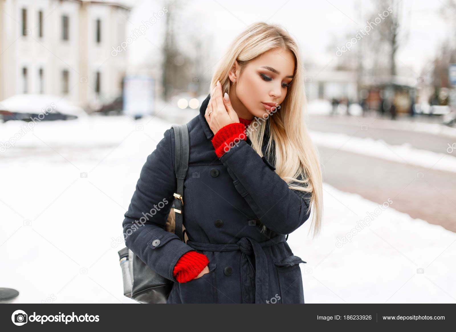 22eb2cfbf8a1 Bella ragazza alla moda in un cappotto alla moda con un sacchetto che cammina  nella città un giorno di inverno– immagine stock