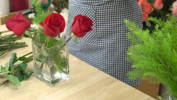 Floristin schneidet Blumen und arrangiert schöne Blumen in einer Glasvase