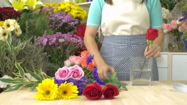 Dolly Shot der Floristin beim Schneiden und Arrangieren von Blumen in einer Glasvase