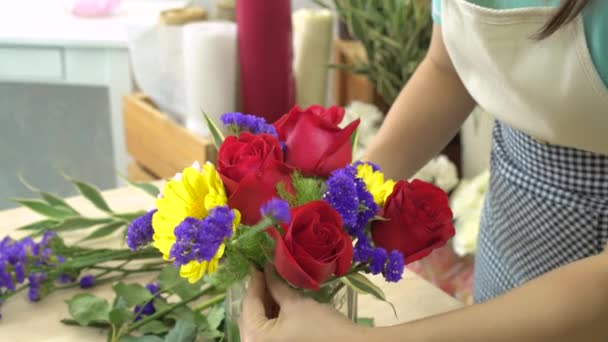 Florist woman cutting flowers and arranging beautiful flowers in a glass vase