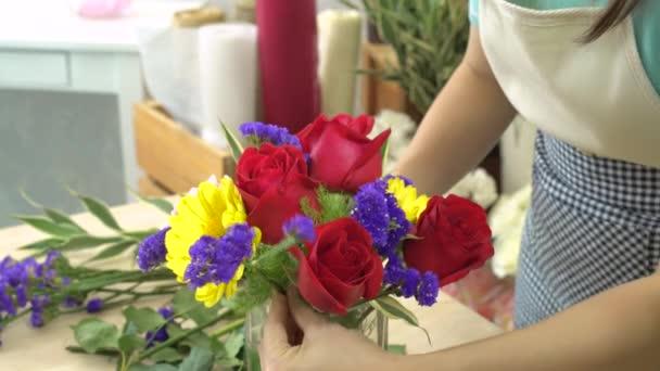 Květinářství stříhací květiny a aranžování krásných květin do skleněné vázy