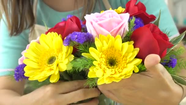 Close up shot of florist woman arranging beautiful flowers in a glass vase