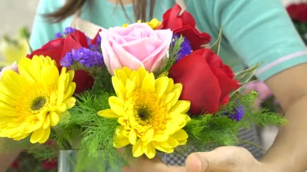 Közelről lövés virágárus nő megszervezése szép virágok egy üvegvázában