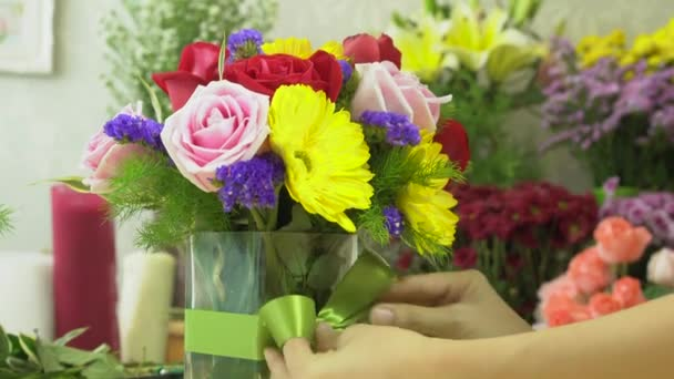 Florist woman finished to arranging flowers with tying ribbon on a glass vase