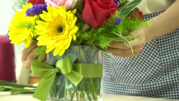 Květinářství dokončoval květiny s vázáním stuhou na skleněnou vázu