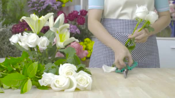 Dolly shot of florist woman cutting stems of white roses