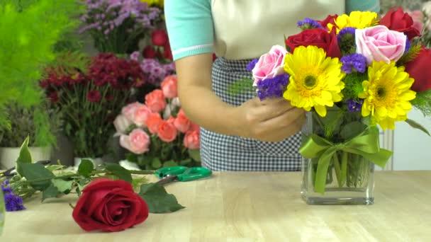 Dolly lövés a virágüzlet nő kész megszervezése virágok egy üvegvázában