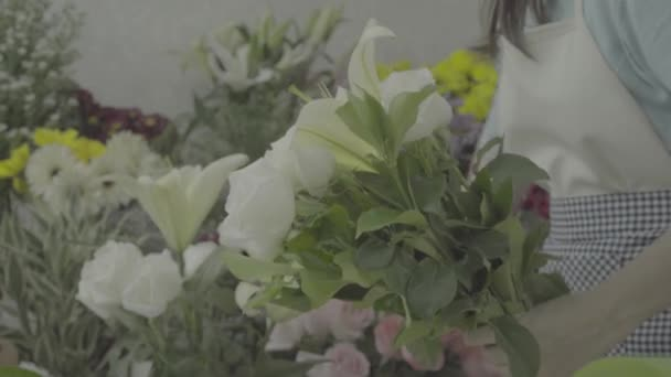 Florist woman arranging a beautiful bouquet with white flowers, ungraded tone