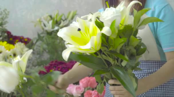 Florist woman arranging a beautiful bouquet with white flowers
