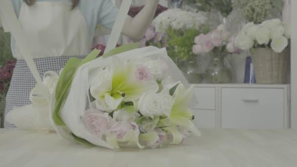 Dolly Shot von Blumenhändlerin, die Schleife an einem Blumenstrauß bindet, ungraded Ton