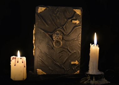 black magic book and two burning candles