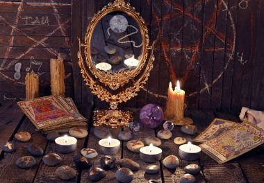 Magic ritual with ancient runes, mirror, tarot cards and candles