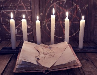 Magic book with pentagram and evil candles for occult ritual