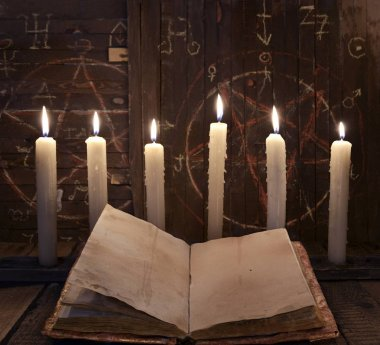 Black magic ritual with burning candles and open book against wooden background