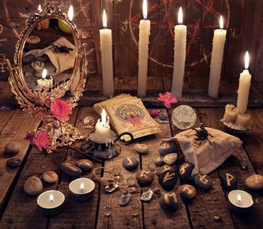 Mystic ritual with burning candles, magic mirror, flowers and the tarot cards