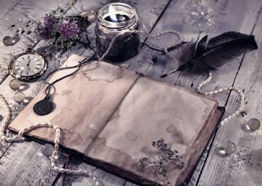 Retro styled still life with old diary, black candle and mystic objects