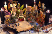 Open book with copy space, herbs and berries, black candle and magic objects on witch table
