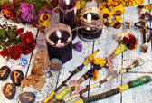 Magic wands, black candles, flowers and moth on witch table