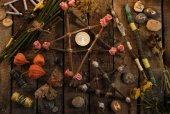Pentagrams with magic wands, moth, runes and flowers on witch table, top view.j