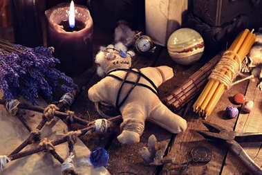Voodoo doll, pentagram and magic objects on witch table. Occult, esoteric, divination and wicca concept. Mystic and vintage background