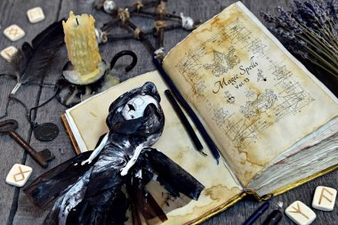 Scary doll, old book with black magic spells and runes on witch table. Occult, esoteric, divination and wicca concept. Halloween vintage background