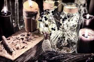 Evil book with black candles, glass bottles, poison berries and herbs on witch table. Halloween, occult, esoteric and wicca concept. Vintage background stock vector