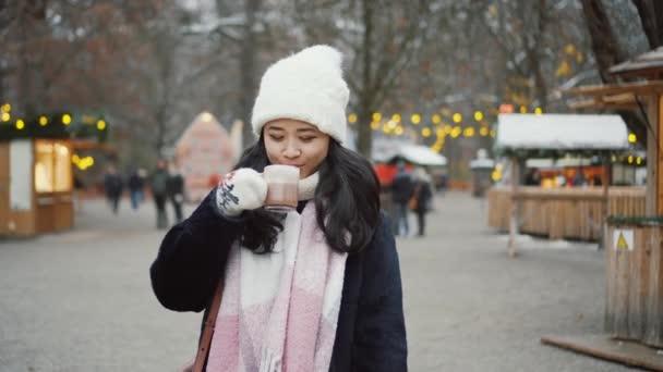 Hübsche junge Frau trinkt draußen auf dem Weihnachtsmarkt in Europa Glühwein. Nettes Mädchen trägt weißen Hut und Fäustlinge im Winter, trinkt heißen Kaffee oder Schokolade neben mit Lichtern geschmückten Baum