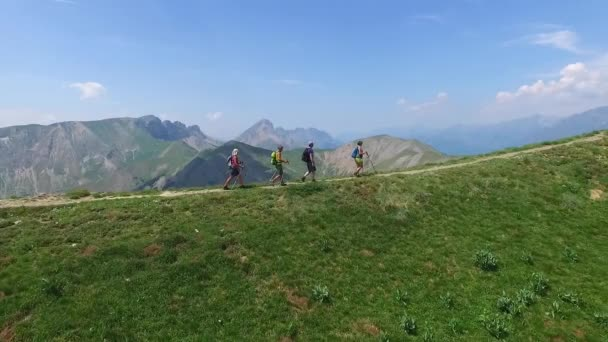 Group of tourists hiking the mountain peak, climbers reached the top. Four hikers walk on the edge of high mountain range. Aerial view of trekking travelers in summer, alpine nature in Alps