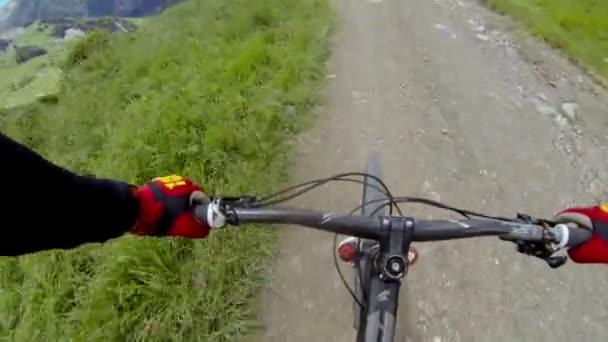 Jízda na horském kole, sjezd na kole. Ruce jezdce. Řídí sportovní motorkář. Sestup na speciální stezce dolů