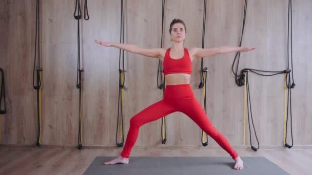 Csinos fiatal lány jógázik odabent. Stretching, fitness wellness órán. Öngondoskodás és aktív életmód koncepció. A lány piros inget és nadrágot visel. Jóga ászana professzionális tanártól.