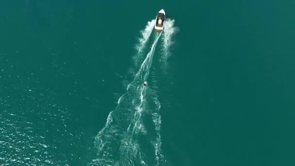 Letecký pohled na vodní lyžování s motorovým člunem na moři s modrou vodou. Vodní sporty v létě, aktivita na dovolené. Jízda na wakeboardingu za lodí.