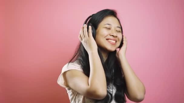 Fröhlich unbeschwertes asiatisches Mädchen, das mit Kopfhörern Musik hört, lächelt und tanzt. Ziemlich schöne junge Frau auf rosa Hintergrund. Emotionen, moderner Lebensstil der Millennials.