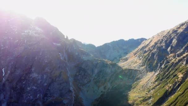 Hory při západu slunce, sluneční paprsky svítí zpoza vrcholků a vrcholků.