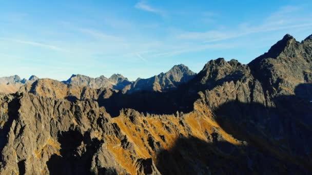 Západ slunce na skalnatých vrcholcích hor. Ostré vrcholky doletu ozářeny sluncem ve večerních hodinách.