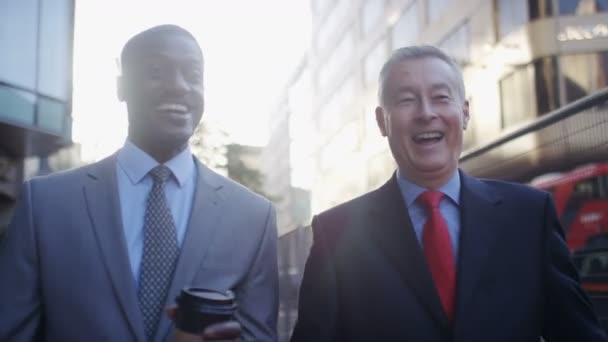 Dva obchodní muži chodí a mluví na ulici