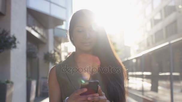Atraktivní mladá žena chůze ve městě pomocí její telefon, zpomalené