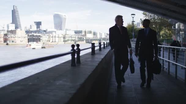 4 k dvou obchodních muži chodí a mluví s městem za nimi v dálce